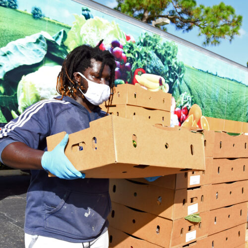 Volunteer holding box of food at mobile food pantry